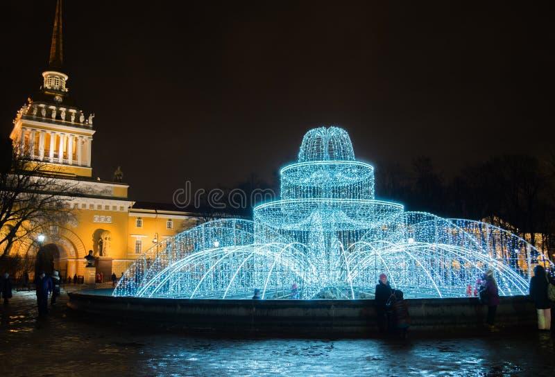 圣彼德堡,俄罗斯- 2017年12月31日:从光亮的火的喷泉在海军部前面的正方形 St Petersbu 图库摄影