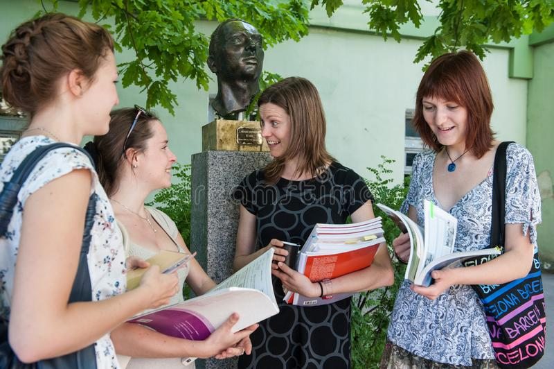 圣彼德堡,俄罗斯- 2018年6月10日:州立大学的一位西班牙语老师在庭院里咨询学生 四 免版税库存照片