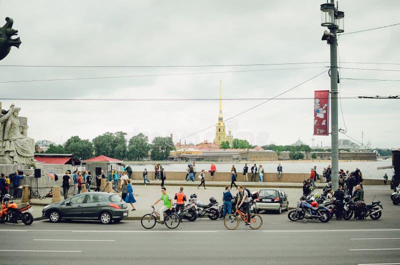 圣彼德堡,俄罗斯- 2018年7月08日:摩托车骑自行车的人和骑自行车者在圣彼德堡街道上  免版税库存照片