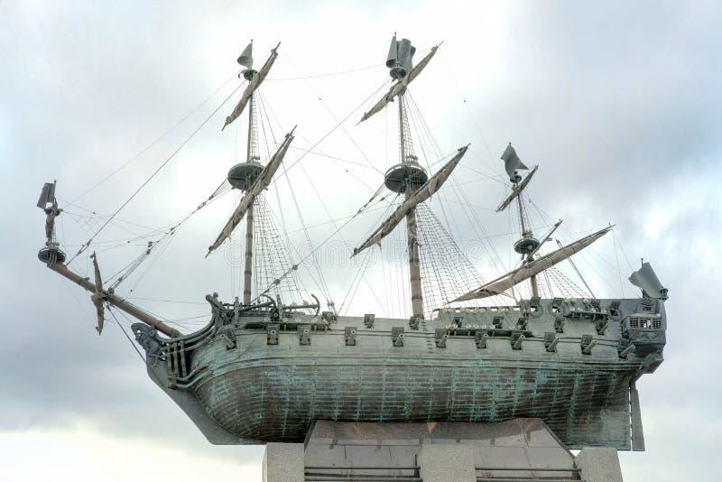 圣彼德堡,俄罗斯- 2018年4月03日-对第一艘俄国战舰波尔塔瓦的古铜色纪念碑反对多云天空 纪念 库存照片