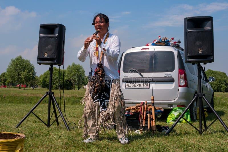 圣彼德堡,俄罗斯- 2016年6月26日:作为印地安人打扮的卖艺人演奏长笛 库存照片