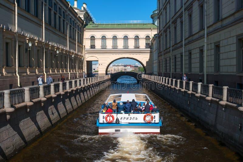 圣彼德堡,俄罗斯- 2016年5月8日:游船沿冬天运河移动在偏僻寺院附近 免版税库存图片