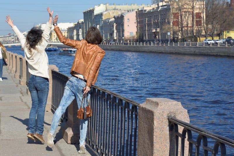 圣徒的Peteresburg俄罗斯少女游人在一好日子享受夏天并且招呼在Fontanka河的观光的小船, 库存照片