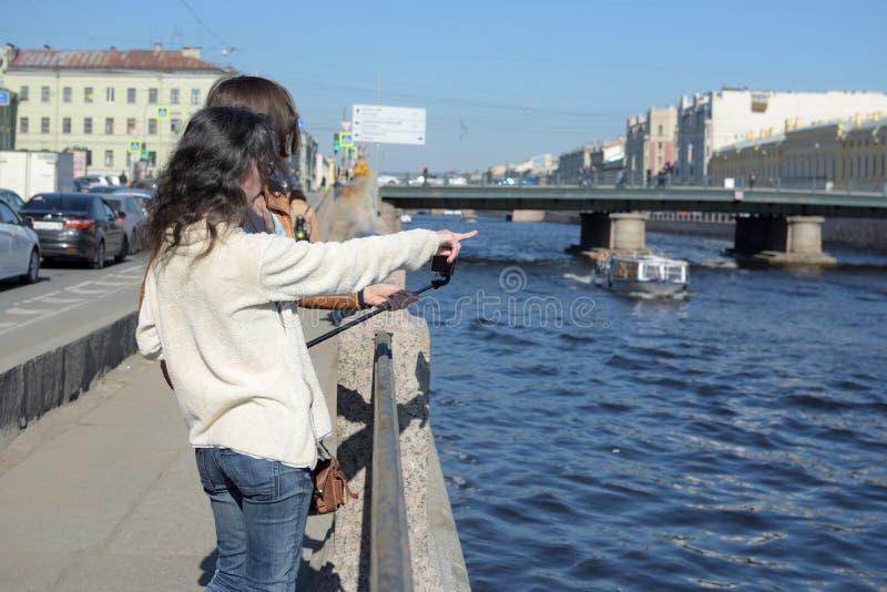 圣徒的Peteresburg俄罗斯少女游人在一好日子享受夏天并且招呼观光的小船 免版税库存图片