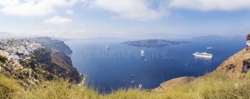 圣托里尼岩石海岸线的全景有资本的Fira图片,希腊和数游轮 图库摄影