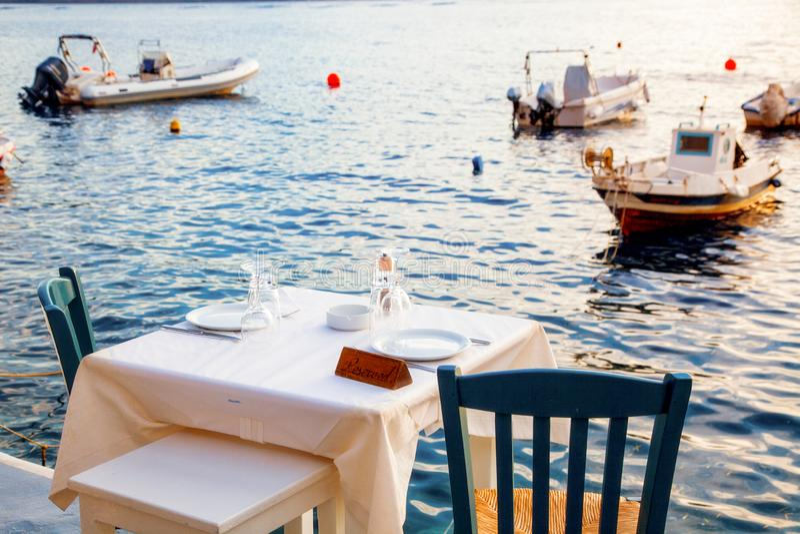 圣托里尼海边浪漫的晚餐桌 免版税库存图片