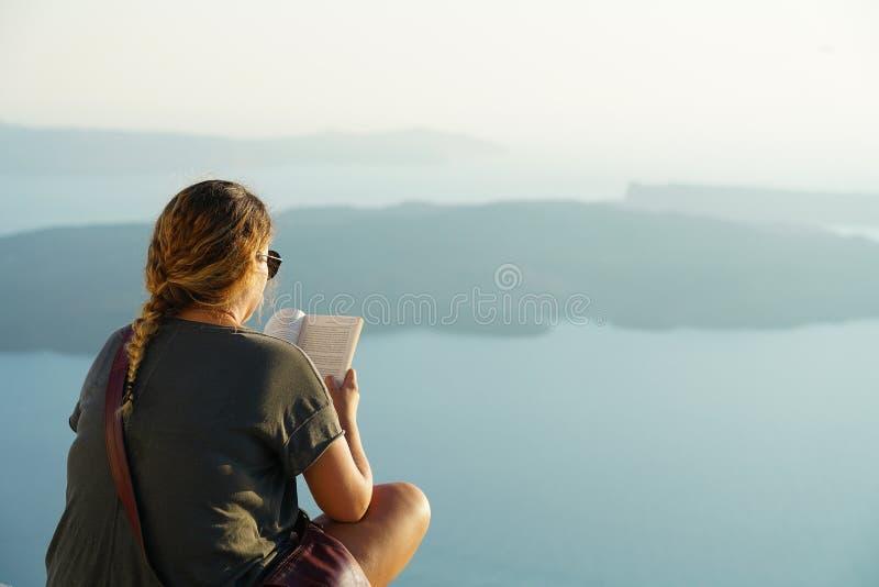 圣托里尼,希腊,2018年9月21日,游人放松读在日落的一本书 免版税库存图片