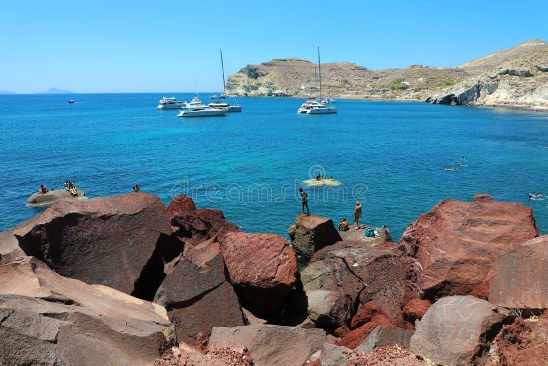 圣托里尼,希腊- 2018年7月21日:沐浴者潜水在红色海滩在圣托里尼,希腊火山岛  库存照片