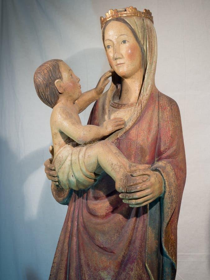 圣母玛丽亚的木雕象有小的耶稣在她的胳膊ins中 库存图片