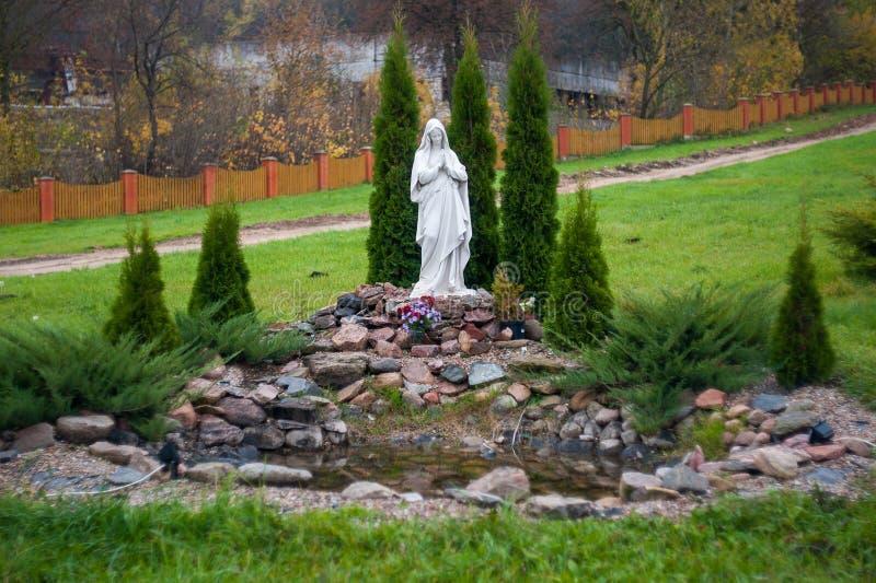 圣母玛丽亚,穿着考究的植被的雕象 免版税图库摄影