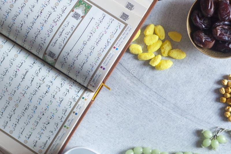 圣洁古兰经、念珠,Iftar甜点和干果子与一杯水 在视图之上 平的位置照片 库存图片