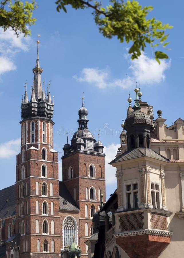 圣玛丽的我们的夫人Assumed大教堂教会到天堂里在大广场的克拉科夫和布料霍尔的部分在前面的 免版税库存图片