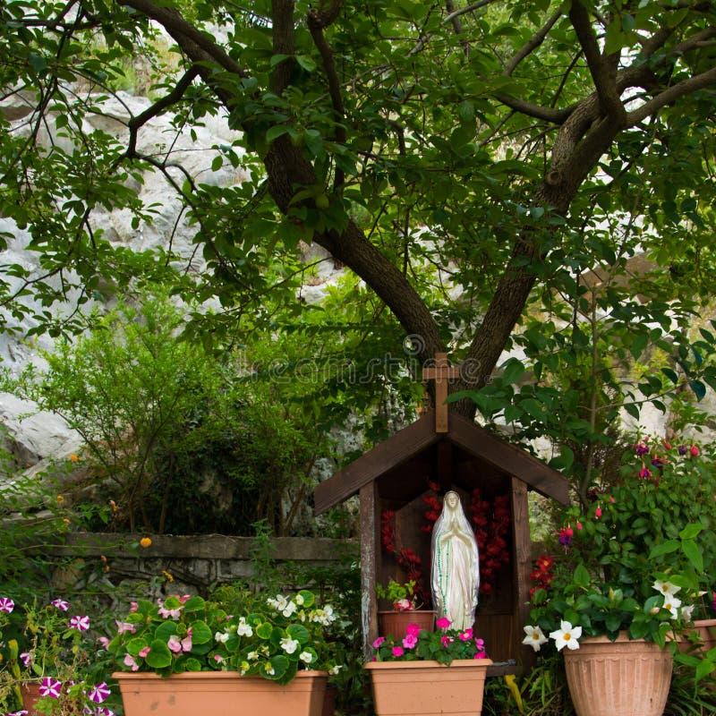 圣玛丽雕象在教会的庭院里 免版税库存图片