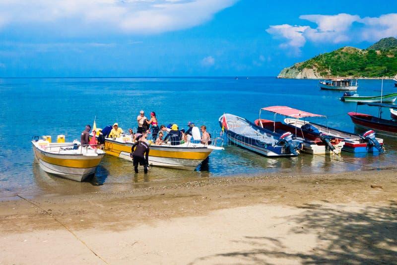 圣玛尔塔,哥伦比亚-双十国庆, 2017年:航行在一个caribean海滩的一条小船的未认出的游人 哥伦比亚taganga 库存照片
