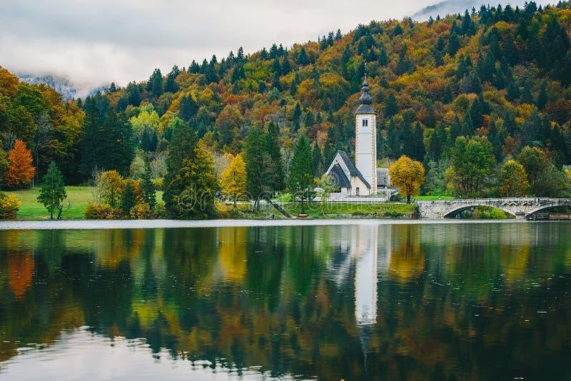 圣约翰著名教会五颜六色的秋季场面出色的意见浸礼会教友, Bohinj湖, Ribicev Laz, S的旅游村庄 免版税图库摄影