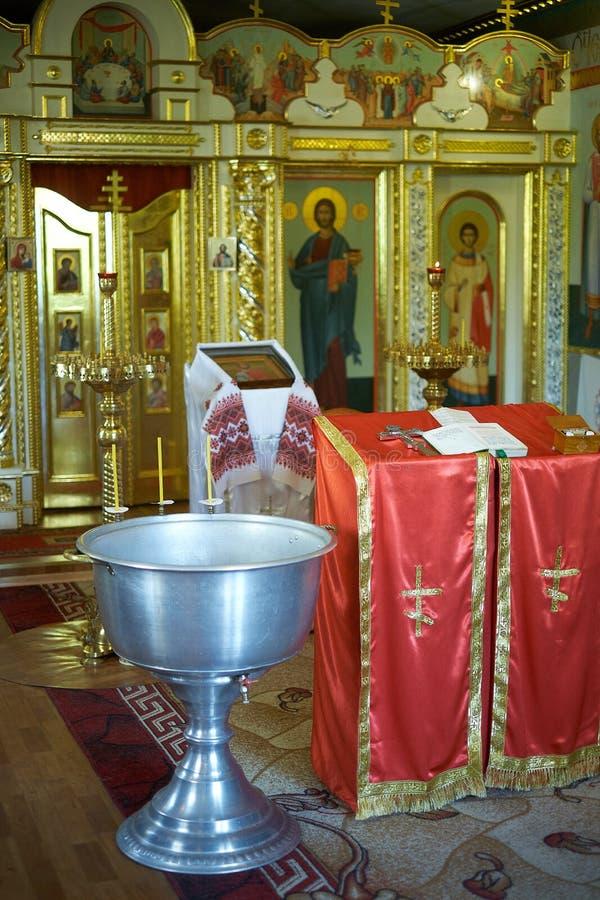圣经、正统十字架和碗为洗礼仪式仪式做准备 库存图片