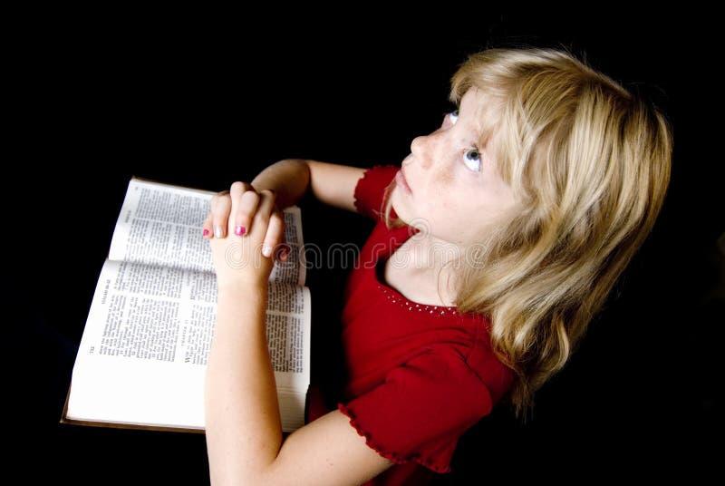 圣经女孩一点在祈祷 图库摄影