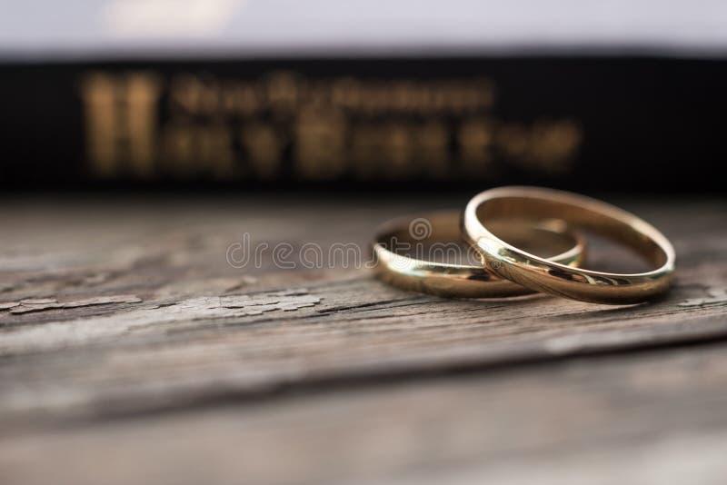 圣经是在两个婚戒休息的基地 免版税图库摄影