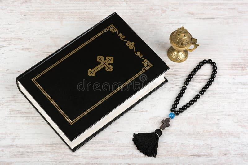 圣经,与十字架和香炉的念珠小珠在白色木背景 宗教概念和信念 库存图片
