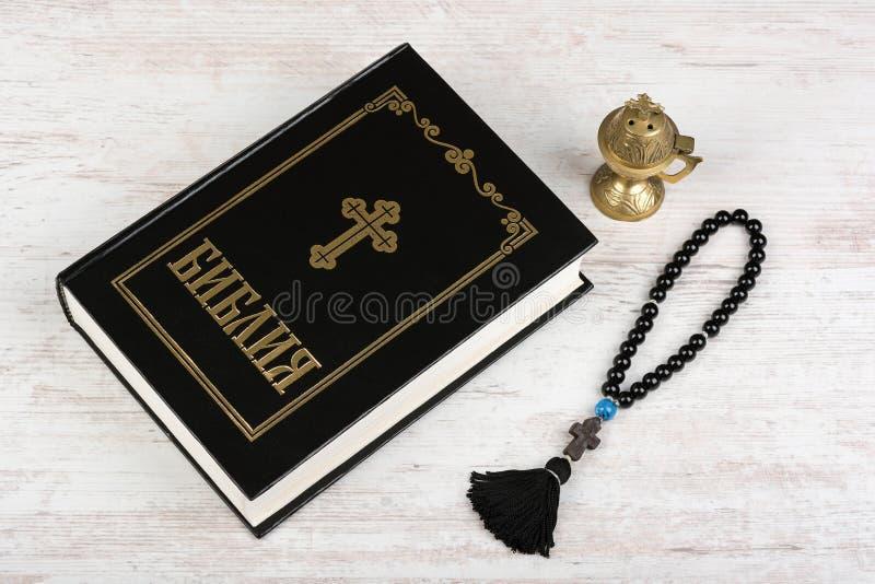 圣经,与十字架和香炉的念珠小珠在白色木背景 宗教 免版税库存图片