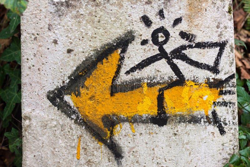 圣詹姆斯方式的标志或者Camino与黄色壳和一个黄色箭头的de圣地亚哥,与对此的一个人 免版税库存照片
