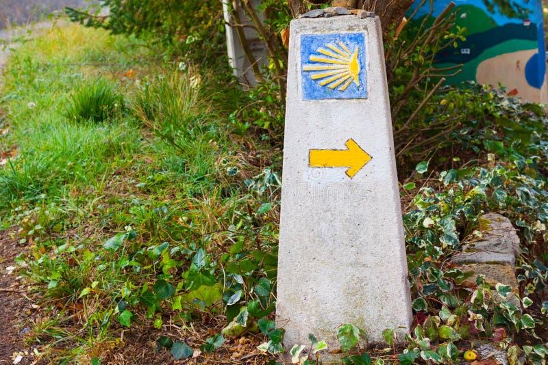 圣詹姆斯Camino de圣地亚哥里程碑典型的方式与一个黄色壳和黄色箭头的 库存图片