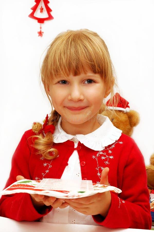 圣诞前夕女孩少许牌照薄酥饼 库存图片