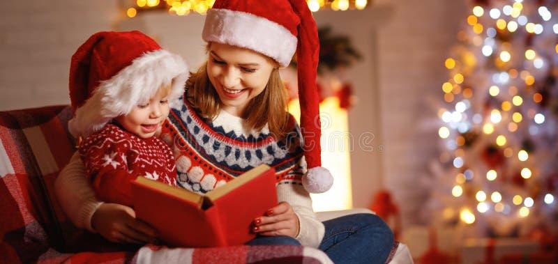 圣诞前夕礼品节假日许多装饰品 家庭母亲和婴孩读书不可思议的书在家 图库摄影