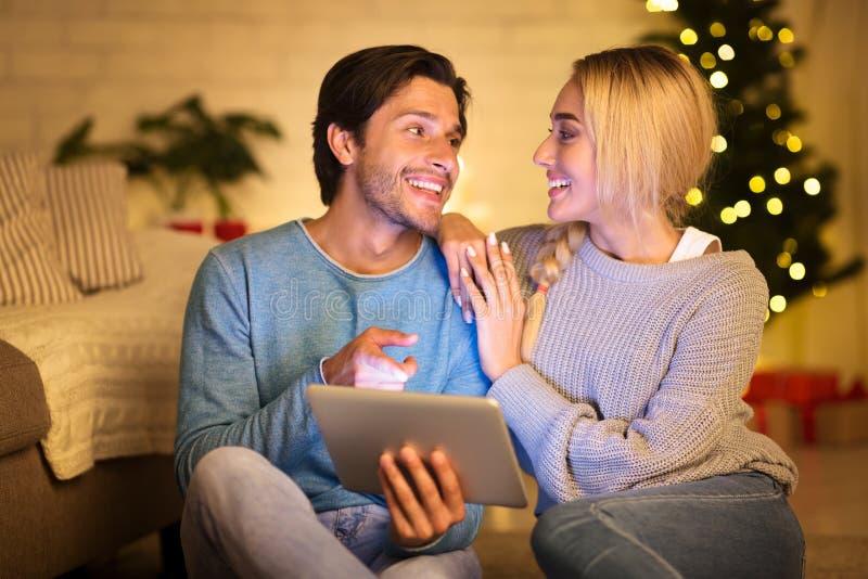 圣诞前夜喜欢的情侣在平板电脑上选片 免版税库存照片