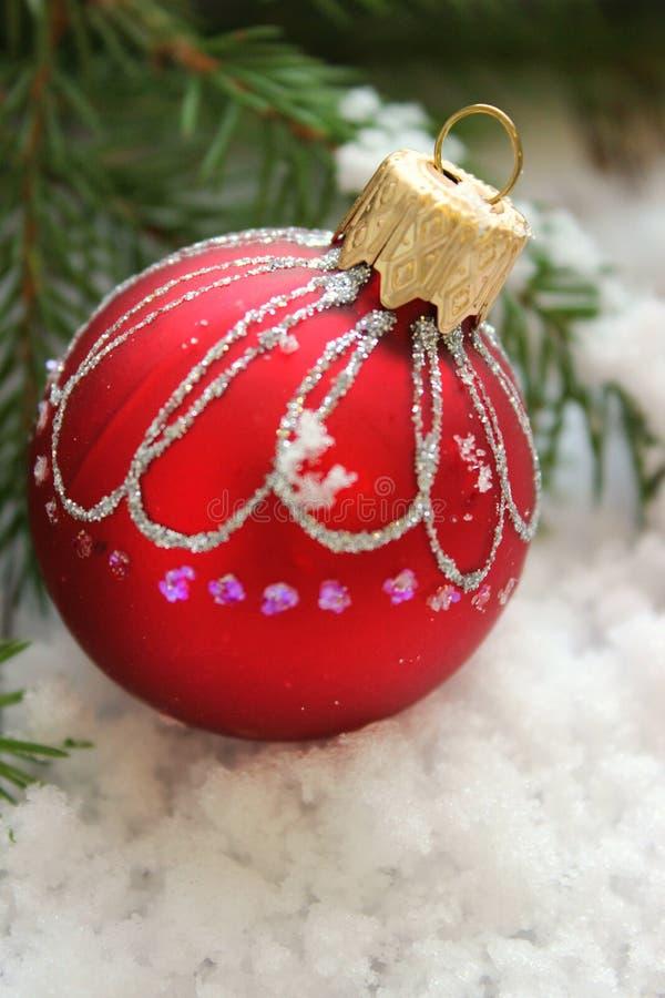 圣诞卡片,与发光的样式的特写镜头圣诞节玩具红色球在冷杉分支围拢的雪 免版税库存照片