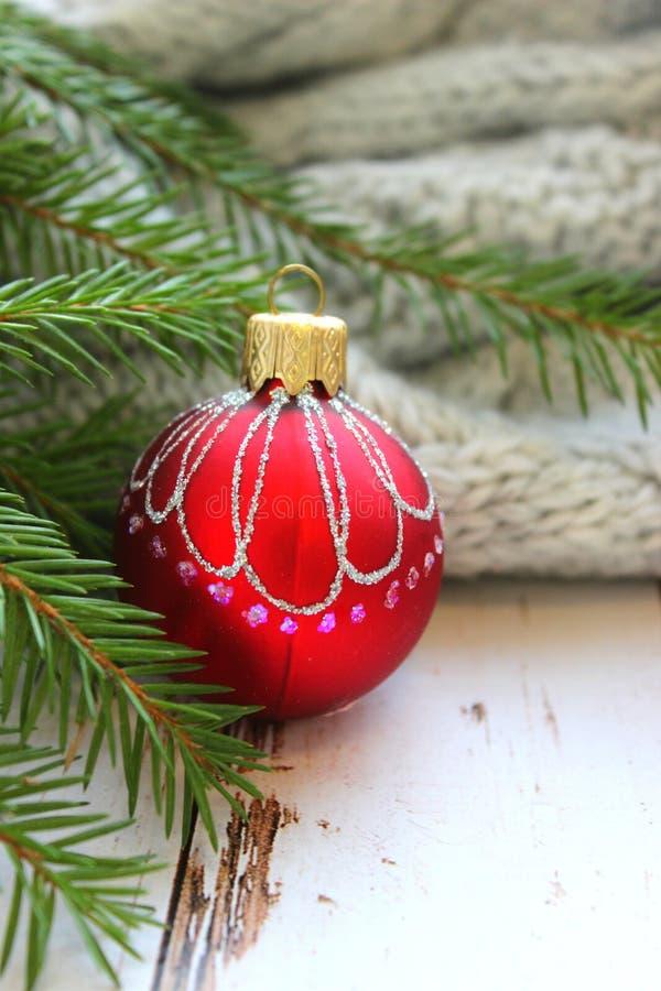 圣诞卡片,关闭-与发光的样式的圣诞节玩具红色shae在冷杉分支围拢的老委员会木背景  库存照片