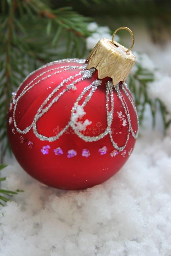 圣诞卡片,关闭-与发光的样式的圣诞节玩具红色shae在冷杉分支围拢的老委员会木背景  免版税图库摄影