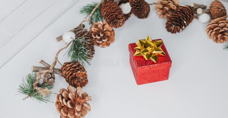 圣诞卡:红色礼物盒和圣诞树在白色分支 免版税库存照片