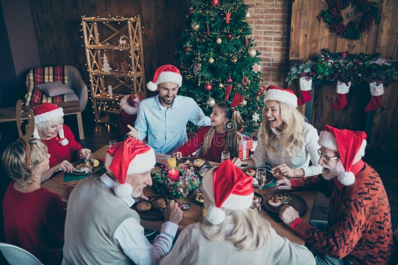 圣诞大团圆聚会席坐桌,圣诞大祭父在圣诞帽子上开玩笑 免版税库存图片