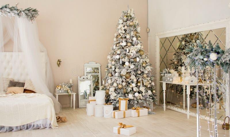 圣诞屋室内设计,圣诞树上装饰着灯光,赠送礼物,玩具是白金色,蜡烛是花环,镜子 库存图片
