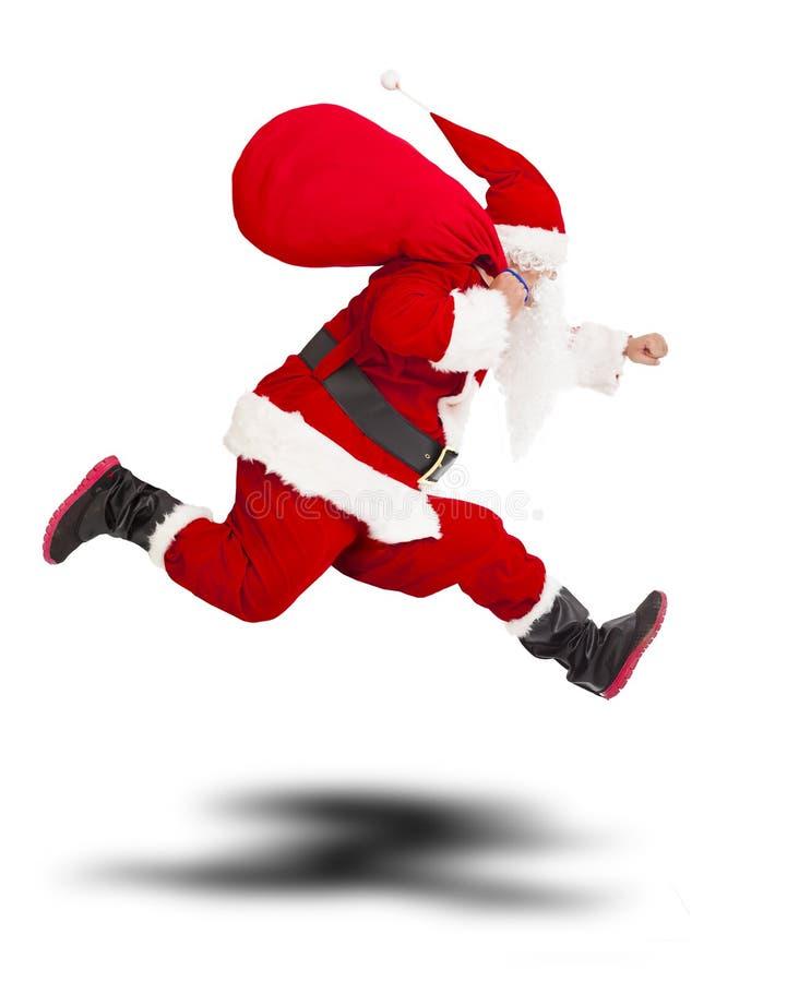 圣诞快乐举行礼物袋子和赛跑的圣诞老人 免版税库存照片
