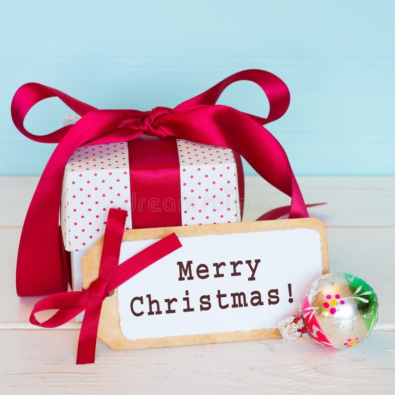 圣诞快乐假日与葡萄酒装饰品,与文本,红色和白色礼物包裹的礼物标记的贺卡与被栓的弓 squar 免版税库存图片