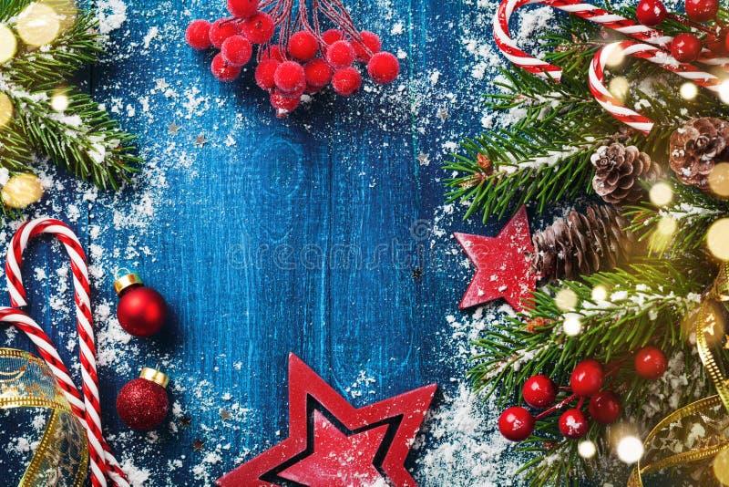 圣诞快乐假日卡片或横幅与多雪的冷杉分支、锥体和欢乐装饰 不可思议的bokeh光 库存照片