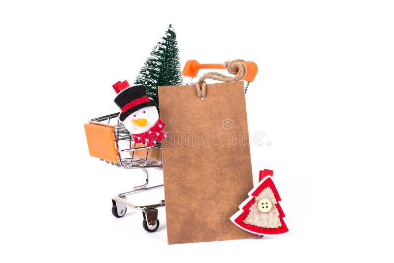 圣诞快乐假日!关闭乐趣滑稽的质朴的圣诞老人雪人红色和绿色树照片在小推挤推车被隔绝的o里面的 免版税库存图片
