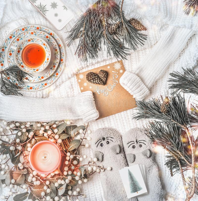 圣诞快乐卡上印着白色针织毛衣、冬花圈、风趣的暖暖的小猫袜、冷杉树枝、燃烧的蜡烛、烤乳香、杯子 库存照片