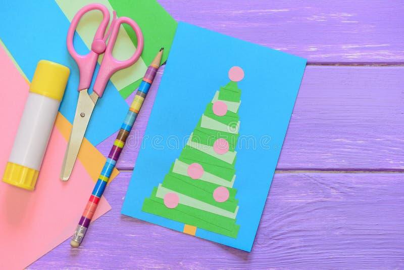圣诞快乐卡片,剪刀,胶浆棍子,铅笔,在紫色木桌上的色纸 乐趣与圣诞树的贺卡 免版税库存照片