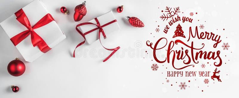 圣诞快乐印刷在与礼物盒和红色装饰的白色背景 免版税库存照片