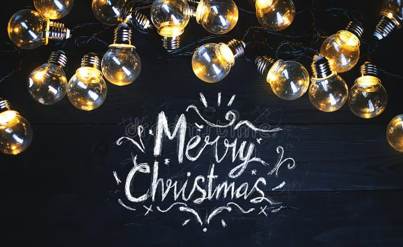 圣诞快乐印刷术在黑木头的电灯泡 免版税库存图片