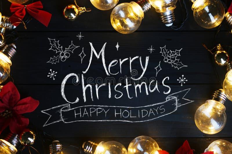 圣诞快乐印刷术电灯泡和红色一品红在Bla 免版税库存图片