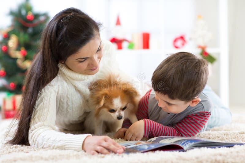 圣诞快乐和新年好 在家读书的妈妈对她逗人喜爱的儿子在圣诞树附近 库存照片