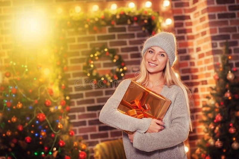 圣诞快乐和新年好!被编织的停留在装饰的假日的帽子和毛线衣的愉快的美丽的微笑的女孩 免版税库存照片