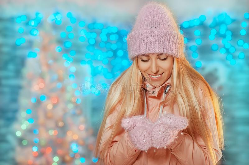 圣诞快乐和新年好!被编织的停留室外和拿着雪的帽子和手套的愉快的美丽的微笑的女孩 库存照片