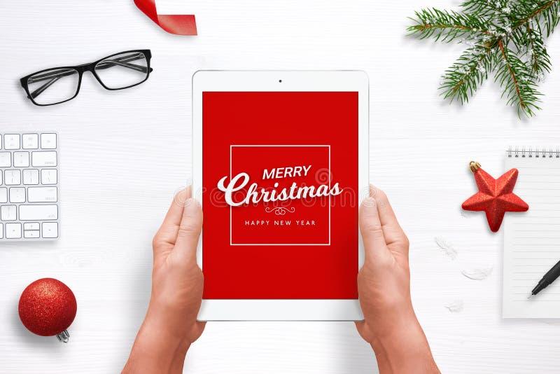 圣诞快乐和新年快乐在片剂的贺卡有红色背景 与圣诞节,新年deco的顶视图构成 免版税库存图片