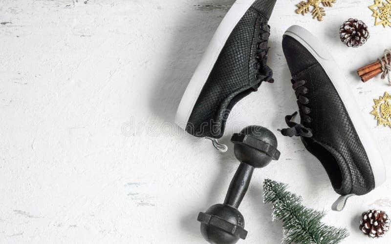 圣诞快乐和新年快乐平的位置健康和活跃生活方式概念的 与哑铃的构成,运动鞋 免版税库存照片