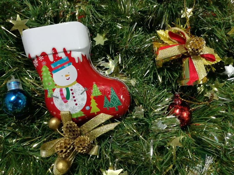 圣诞快乐和新年快乐、雪人袜子罐子箱子、丝带和装饰品装饰与绿色闪亮金属片 库存图片